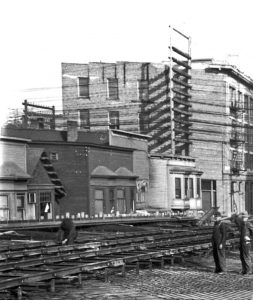"""history prostitution A rare photo of the brothels on the north side of Shore Street, shortly after the relocation of the """"restricted district"""" to Alexander and during construction of the original Georgia Viaduct. City of Vancouver Archives #LGN 1188 (cropped)"""