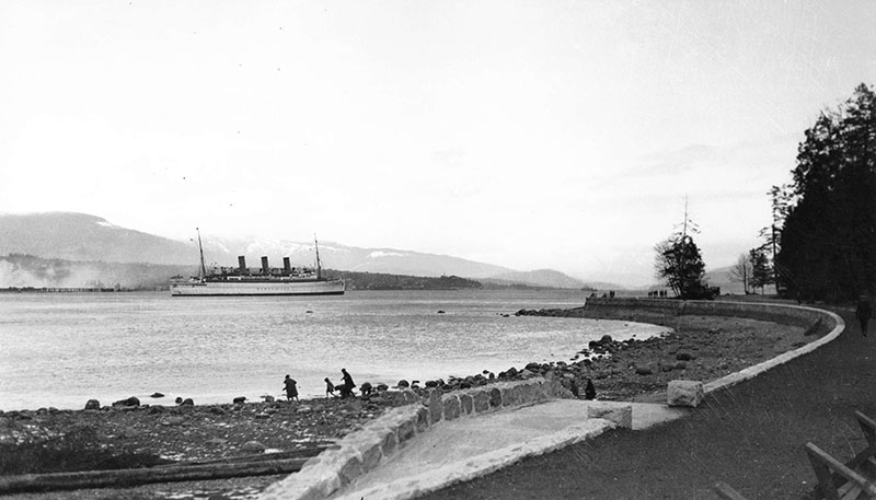 The seawall under construction in 1920, with the Empress of Canada liner entering the harbour. Photo by Stuart Thompson, City of Vancouver Archives #99-1476.