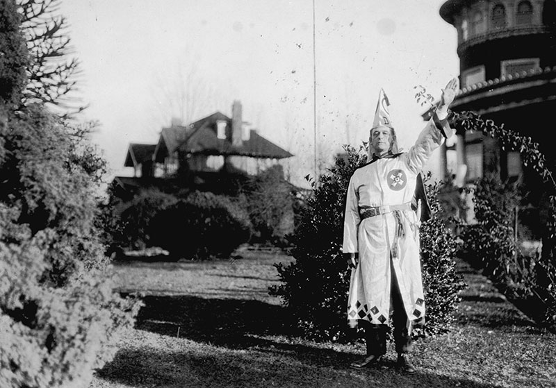 Ku Klux Klan member outside their Shaughnessy headquarters at Glen Brae Manor in 1925. Today it's Canuck Place Children's Hospice. Photo by Stuart Thomson, City of Vancouver Archives #99-1499.