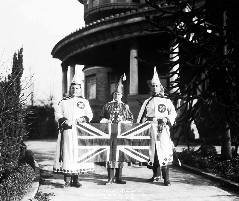 """The """"Imperial Klouncil"""" of the KKK outside Glen Brae Manor, holding a Union Jack. Photo by Stuart Thomson, City of Vancouver Archives #99-1496."""