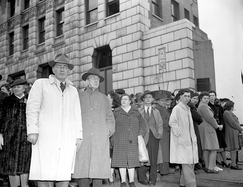 The Marine Building looming over onlookers following the Greenhill Park explosion in 1945. The Greenhill Park was a 10,000 ton freighter with combustible cargo that exploded in Vancouver Harbour, killing 8 longshoremen and injured 19 others. Seven fire fighters were also hospitalized. The blast blew out windows for blocks away and many people initially feared the Japanese were attacking. It remains the worst disaster in Vancouver's waterfront history. Photo by Don Coltman, City of Vancouver Archives #586-3601.