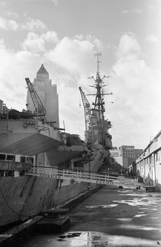 The Marine Building looking over the British aircraft carrier HMS Glory in 1945. Photo by James Crookall, City of Vancouver Archives #260-1537.