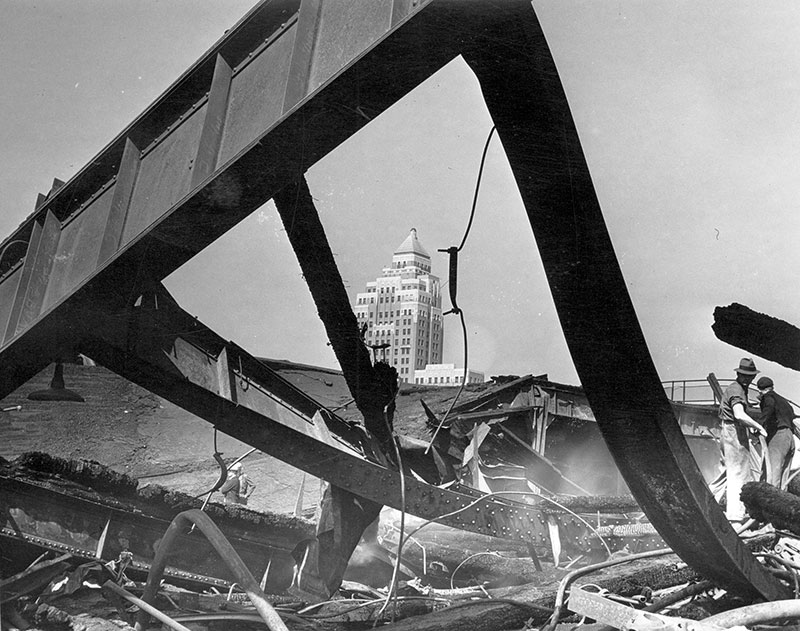 The Marine Building has witnessed some history over the past 88 years. Here it is through the charred remains of the CPR's Pier D, which was destroyed in a spectacular fire in 1938. Photo by Stan Williams, City of Vancouver Archives #Can P61.2.