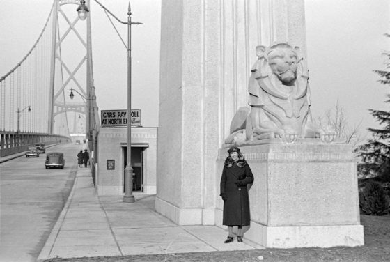 Woman stands at the entrance to the Lion's Gate Bridge